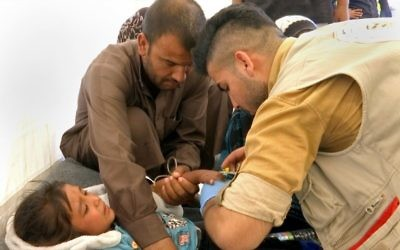 In this screen grab from video, a man comforts his daughter as a doctor treats her after she was taken ill with suspected food poisoning in the Hassan Sham U2 camp for displaced people east of Mosul, Iraq, June 13, 2017. (AP/Balint Szlanko)