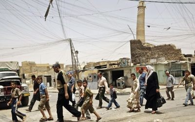 Residents walk past the crooked minaret of the iconic al-Nuri mosque in Mosul, Iraq, June 8, 2009. (AP Photo/Maya Alleruzzo, File)