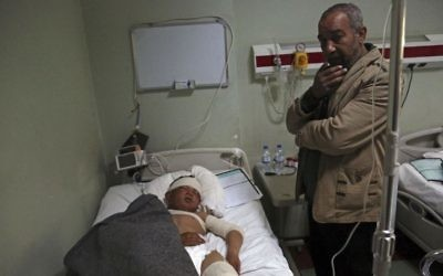 In this Saturday, March 4, 2017 file photo, Nazim Hamid stands next to his injured son Yasir, 11, a victim of a possible IS chemical attack in a hospital Irbil, Iraq (AP Photo/ Khalid Mohammed, File)