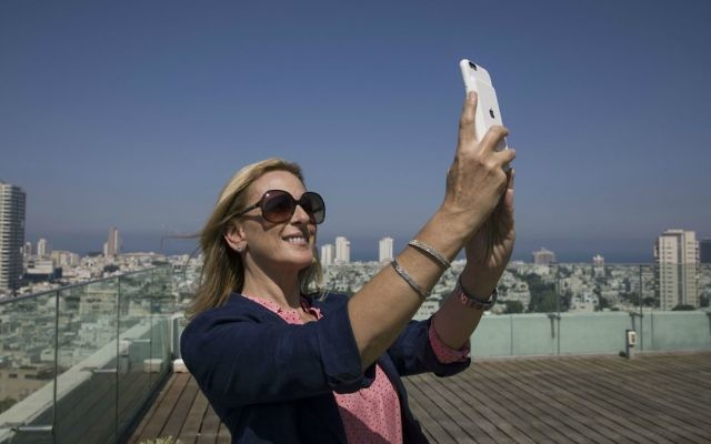 American Oscar-winning actress Marlee Matlin takes a selfie on the rooftop of the Tel Aviv municipality Monday, June 19, 2017. (AP Photo/Tsafrir Abayov)