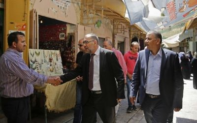 In this Monday, June 5, 2017 photo, the Mayor of Hebron Tayseer Abu Sneineh greets a shopkeeper at a market in the West Bank city of Hebron. (AP Photo/Nasser Shiyoukhi)
