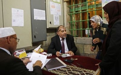 In this Monday, June 5, 2017 photo, the Mayor of Hebron Tayseer Abu Sneineh talks to people who have requests for help, inside a mosque in the West Bank city of Hebron. (AP/Nasser Shiyoukhi)