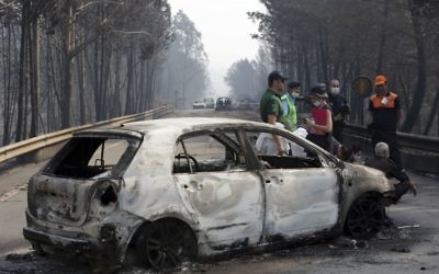 Police investigators stand by a burnt car on the road between Castanheira de Pera and Figueiro dos Vinhos, central Portugal, June 18 2017. (AP/Armando Franca)