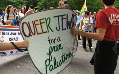 Protesters at the June 4, 2017 New York Celebrate Israel Parade march with the Jewish Queer Youth and hold up a sign saying 'Queer Jews for a Free Palestine.' (Mordechai Levovitz)