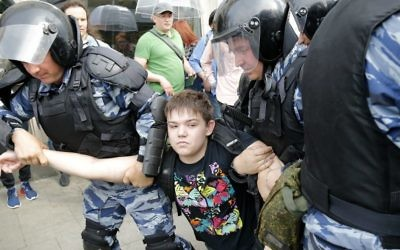 A young demonstrator is apprehended by riot police during a demonstration in downtown Moscow, Russia, Monday, June 12, 2017. (AP Photo/Alexander Zemlianichenko)