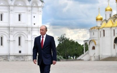 Russian President Vladimir Putin walks along the Cathedral Square of the Kremlin, to take part in a holiday reception in Moscow, Monday, June 12, 2017. (Alexei Druzhinin/Sputnik, Kremlin Pool Photo via AP)