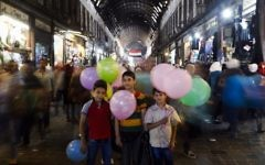 In this May 18, 2017, photo, Syrian boys pose for a picture as they sell balloons at the Hamadiyah market, in the Old City of Damascus, Syria. (AP Photo/Hassan Ammar)