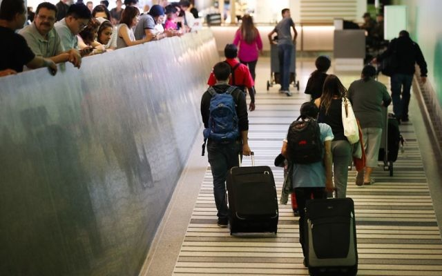 Travelers make their way up the arrival ramp at the Tom Bradley International Terminal at the Los Angeles International Airport Thursday, June 29, 2017, in Los Angeles (AP Photo/Jae C. Hong)