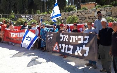 Beit El residents hold signs at a protest outside the Prime Minister's Office in Jerusalem on June 19, 2017. (Courtesy)