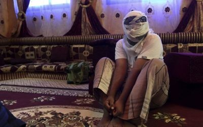 A former detainee shows how he was kept in handcuffs and leg shackles while held in a secret prison at Riyan airport in the Yemeni city of Mukalla in this May 11, 2017 photo. (AP Photo/Maad El Zikry)