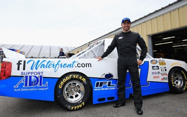 Alon Day, driver of the #71 FLwaterfront.com Chevrolet, poses in the garage area during practice for the NASCAR Camping World Truck Series UNOH 175 at New Hampshire Motor Speedway on September 23, 2016 in Loudon, New Hampshire. (Chris Trotman/NASCAR via Getty Images/JTA)