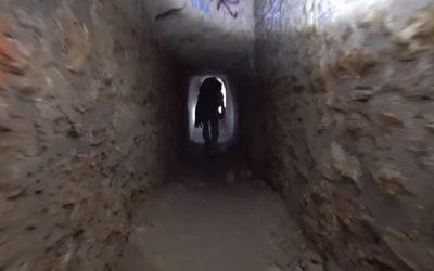 A man walks through catacombs under Paris (YouTube screenshot)