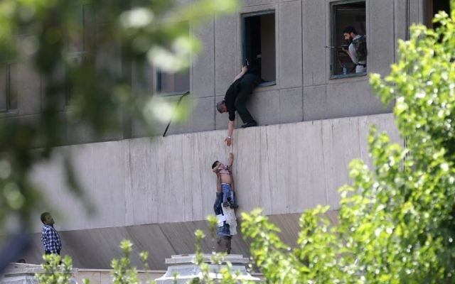 Iranian policemen evacuate a child from the parliament building in Tehran during a terror attack, June 7, 2017. (AFP PHOTO / FARS NEWS / OMID VAHABZADEH)