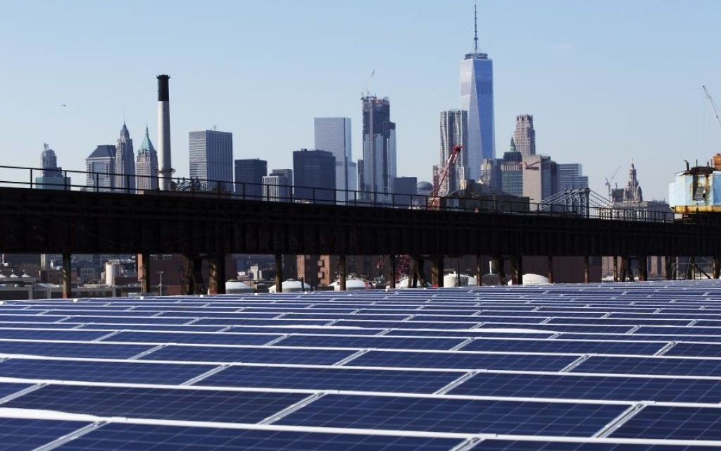 In this February 14, 2017 photo, taken against the backdrop of the Manhattan skyline, a rooftop is covered with solar panels at the Brooklyn Navy Yard in New York. (AP Photo/Mark Lennihan)
