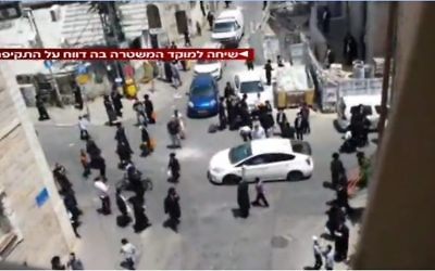 File: Ultra-orthodox men rioting in Jerusalem's Mea Shearim neighborhood against a soldier who arrived for weekend furlough in uniform on Friday, June 9 2017. (Screen capture Channel 2)