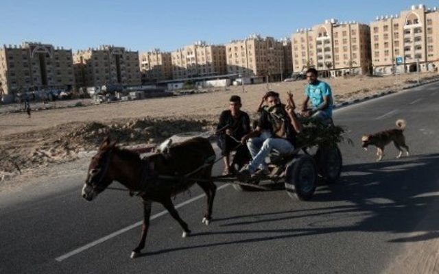 Palestinians ride a donkey-pulled-cart past residential units funded by Qatar in Khan Younis in the southern Gaza Strip, June 6, 2017. (AFP PHOTO / SAID KHATIB)