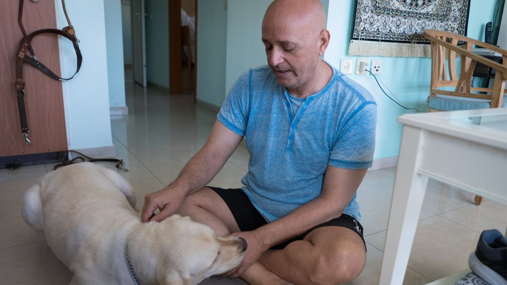 Herzl Cohen, with his guide dog Todd, at his Ramat Gan apartment, June 1, 2017. (Luke Tress/Times of Israel)