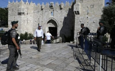 A Palestinian man walks past Israeli security forces standing guard at Damascus Gate outside Jerusalem's Old City on May 31, 2017. (AFP Photo/Ahmad Gharabli)