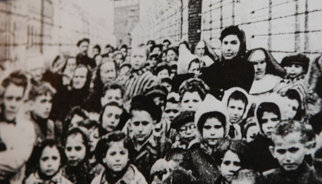 Michael Bornstein is carried out of Auschwitz in his grandmother's arms. Michael is the one to the left of the child with the pointed hood. (Courtesy)