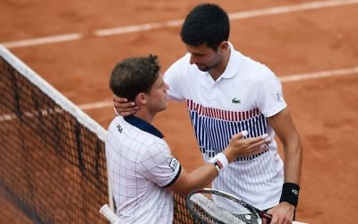 Diego Schwartzman, left, is congratulated by Novak Djokovic after their thrilling five-set French Open match in Paris won by Djokovic, June 2, 2017. (Lionel Bonaventure/AFP/Getty Images via JTA)
