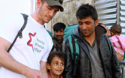 A volunteer with the organization World Jewish Relief works with refugees in Greece. (Minos Alchanati/via JTA)