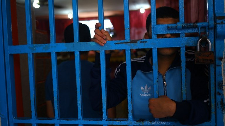 A drug addict stands behind bars at a Hamas-run prison in Gaza City on May 10, 2017. (AFP Photo/Mohammed Abed)