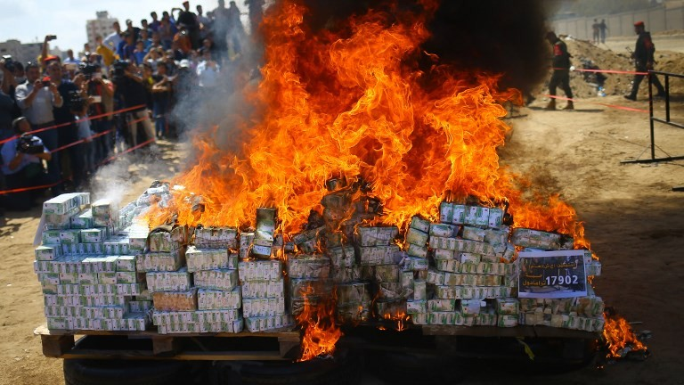 A pile of confiscated bars of hashish seized since the beginning of the year being burnt in Gaza City, on May 11, 2017. (AFP Photo/Mohammed Abed)