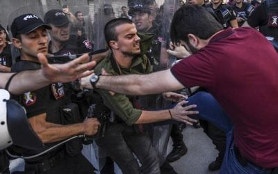 A plain-clothes police officer kicks a member of a group of LGBT rights activist as Turkish police prevent them from going ahead with a Gay Pride annual parade on June 25, 2017, in Istanbul. (AFP Photo/Bulent Kilic)