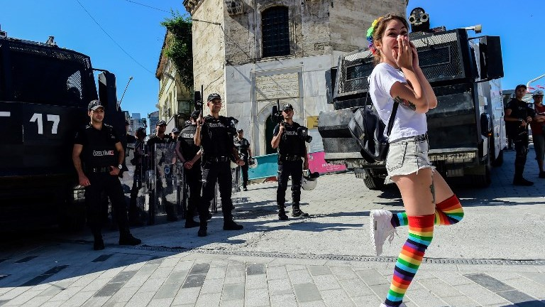 Turkish riot police officers block roads to Istikjlal avenue for LGBT rights activist (C) as they try to gather for a pride parade, which was banned by the governorship, in Istanbul, on June 25, 2017. (AFP Photo/Bulent Kilic)