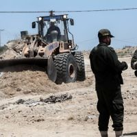 Security forces loyal to the Hamas terror group stand by as bulldozers clear an area for a large buffer zone on the border with Egypt in the southern Gaza strip town of Rafah, on June 28, 2017. (AFP/Said Khatib)