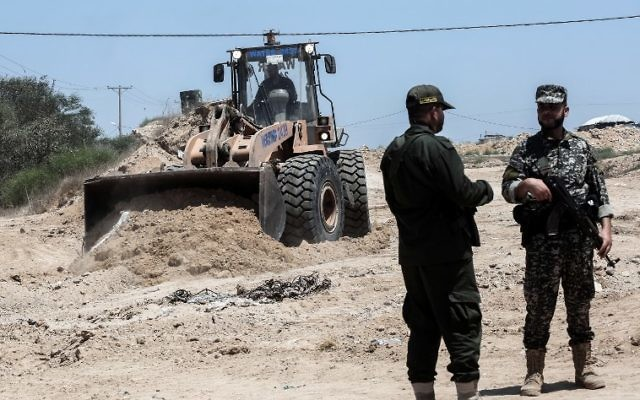 Palestinian security forces loyal to Hamas stand by as bulldozers clear an area for a large buffer zone on the border with Egypt in the southern Gaza strip town of Rafah, on June 28, 2017. (AFP/SAID KHATIB)
