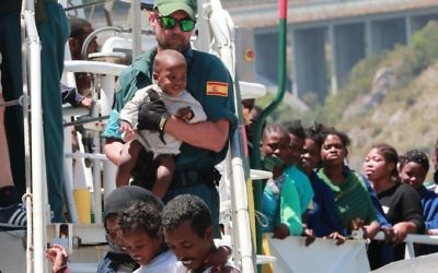 A Guardia Civil officers helps migrants to disembark from the Spanish Guardia Civil Rio Segura Patrol Ship with 1,216 migrants onboard including 256 children and 11 pregnant women, who were rescued in the Mediterranean sea on June 29, 2017, in the port of Salerno, Italy (AFP PHOTO / CARLO HERMANN)