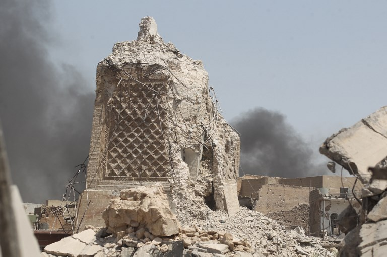 """Smoke billows in the background behind the base of Mosul's destroyed ancient leaning minaret, known as the """"Hadba"""" (Hunchback), in the Old City on June 30, 2017, where Abu Bakr al-Baghdadi gave his first sermon as leader of the Islamic State group and its ancient minaret. (AFP PHOTO / AHMAD AL-RUBAYE)"""