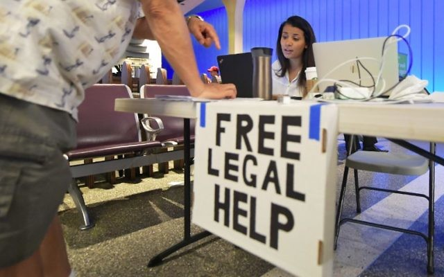 Volunteer lawyer Marwa Rifahie, a civil rights attorney with the Council on American-Islamic Relations, responds to questions from behind a at a table set up at Los Angeles International Airport in Los Angeles, California on June 30, 2017, offering free legal advice. (AFP PHOTO / FREDERIC J. BROWN)