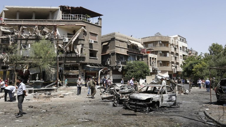 Syrians inspect the site of a suicide bomb attack in Damascus on July 2, 2017. (AFP Photo/Louai Beshara)
