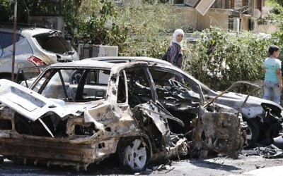 Syrians walk past a charred vehicle at the site of a suicide bombing in Damascus on July 2, 2017. (AFP Photo/Louai Beshara)