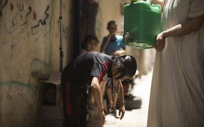 Illustrative: A Palestinian boy cools off with water from a jerrycan held by a man during a heatwave at al-Shati refugee camp in Gaza City on July 2, 2017.  (AFP Photo/Mahmud Hams)