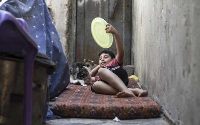 A Palestinian boy uses a plastic plate as a fan during a heatwave at al-Shati refugee camp in Gaza City on July 2, 2017. ( AFP PHOTO / MAHMUD HAMS)