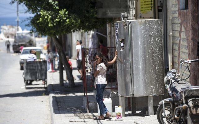 A Palestinian girl fills a jerrycan with water during a heatwave at al-Shati refugee camp in Gaza City on July 2, 2017. (AFP Photo/Mahmud Hams)