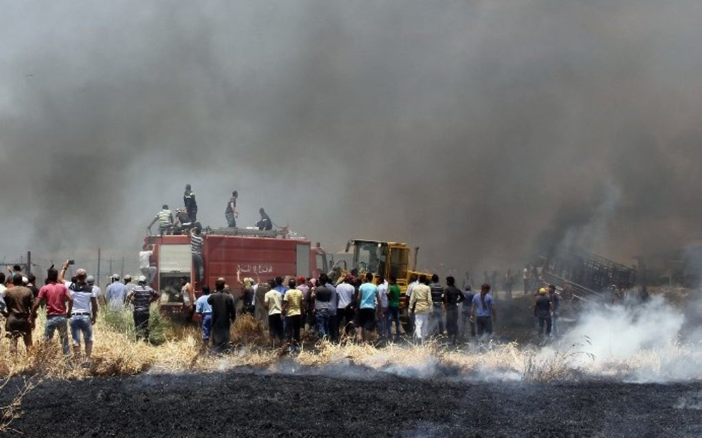 Smoke billows as firefighters attempt to extinguish a massive fire in a camp for Syrian refugees near the village of Qab Elias in the Lebanese Bekaa valley on July 2, 2017. (AFP PHOTO / STRINGER)