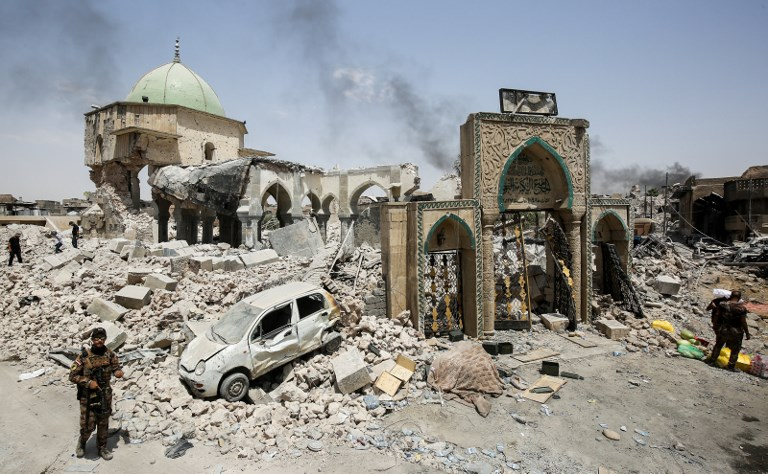 Members of the Iraqi Counter-Terrorism Service (CTS) gather outside the destroyed gate of the Al-Nuri Mosque while others inspect the interiors, in the Old City of Mosul on July 2, 2017, during the Iraqi government forces' offensive to retake the city from Islamic State (IS) group fighters. (AFP PHOTO / AHMAD AL-RUBAYE)