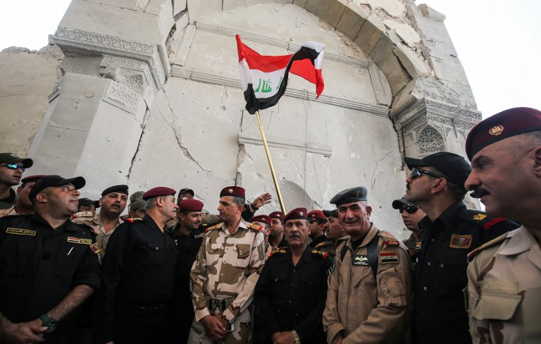 Chief of Staff of the Iraqi Army, Staff Lieutenant-General Othman al-Ghanimi (3rd-L), along with Counter-Terrorism Service (CTS) commander Staff Lieutenant-General Abdul Ghani al-Asadi (2nd-L), gather for a group photo with the Iraqi national flag raised at the site where Abu Bakr al-Baghdadi gave his first sermon as leader of the Islamic State (IS) group in the Grand Mosque of Al-Nuri in 2014, on July 2, 2017, during the Iraqi government forces' offensive to retake the city from IS. (AFP PHOTO / AHMAD AL-RUBAYE)
