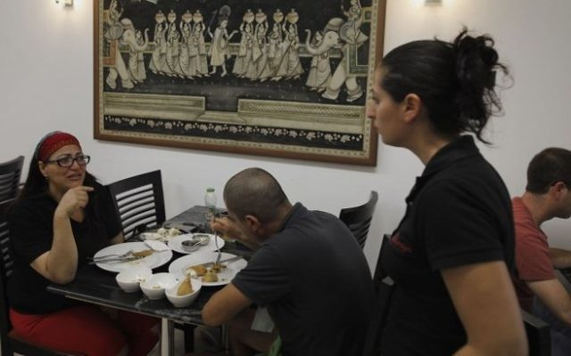 Israelis eat at the Maharaja Indian restaurant in the small city of Ramla, south of Tel Aviv, on July 2, 2017, as the Jewish Indian community in Israel prepare for the visit of the Indian prime minister. (AFP/ MENAHEM KAHANA)