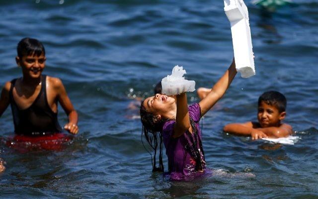 A Palestinian girl laughs while holding a jellyfish in one hand a block of foam in another, as she stands in the Mediterranean sea near al-Shati refugee camp in Gaza City on July 3, 2017. ( AFP PHOTO / MOHAMMED ABED)