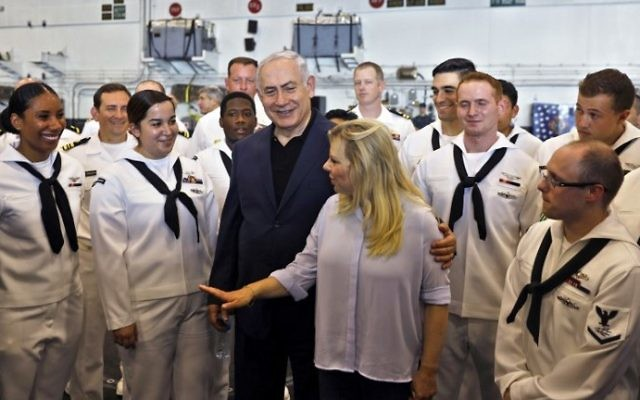Prime Minister Benjamin Netanyahu and his wife Sara  speak with American soldiers during a visit on the US aircraft carrier USS George H. W. Bush, as it docked outside the Haifa port, on July 3, 2017. (AFP Photo/AFP Photo and Pool/Ronen Zvulun)