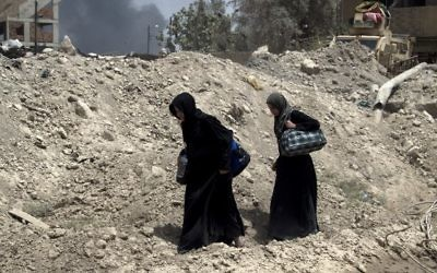 Smoke billows as Iraqi women flee the Old City of Mosul on July 3, 2017, during the government forces' ongoing offensive to retake the city from Islamic State (IS) group fighters. (AFP/Fadel Senna)