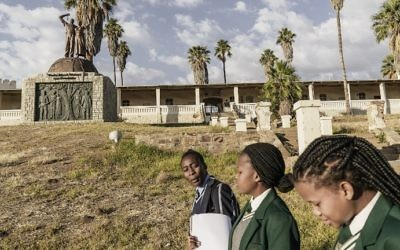 Namibian schoolgirls walk by a memorial in tribute to the victims of the alleged genocide committed by German forces against Herero and Nama people in 1904, on June 20, 2017 in Windhoek, Namibia. (AFP Photo/Gianluigi Guercia)