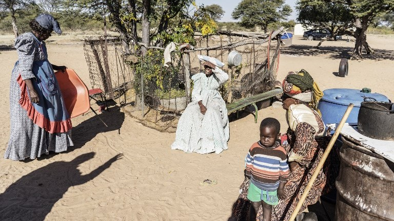Elderly Herero women sit in the yard outside their houses on the outskirts of the impoverished Namibian town of Okakarara on June 22, 2017. (AFP Photo/Gianluigi Guercia)