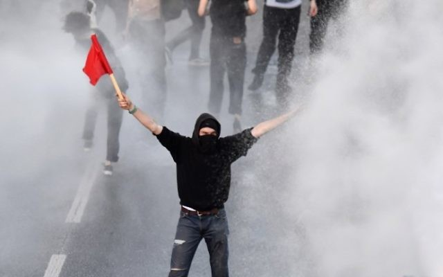 """Police use water cannons towards a protester with a red flag during the """"Welcome to Hell"""" rally against the G20 summit in Hamburg, Germany, on July 6, 2017. (AFP Photo/John Macdougall)"""