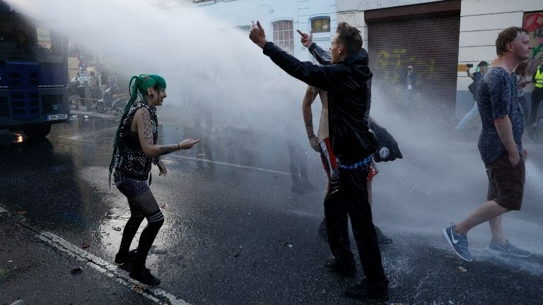 """Riot police use water cannons against demonstrators during the """"Welcome to Hell"""" rally against the G20 summit in Hamburg, Germany on July 6, 2017. (AFP Photo/Odd Andersen)"""